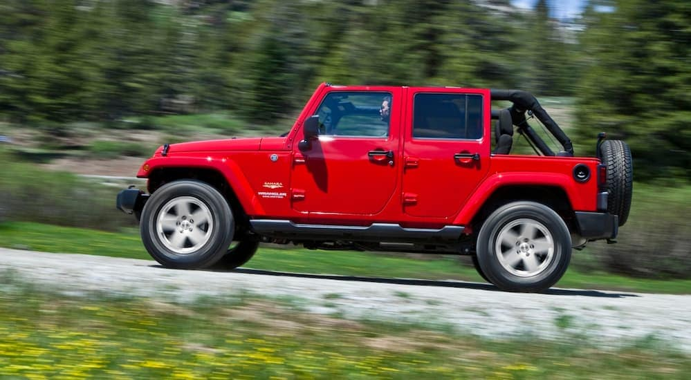 A side view of a red 4-door 2015 Jeep Wrangler driving up a treelined hill near Costa Mesa, CA.
