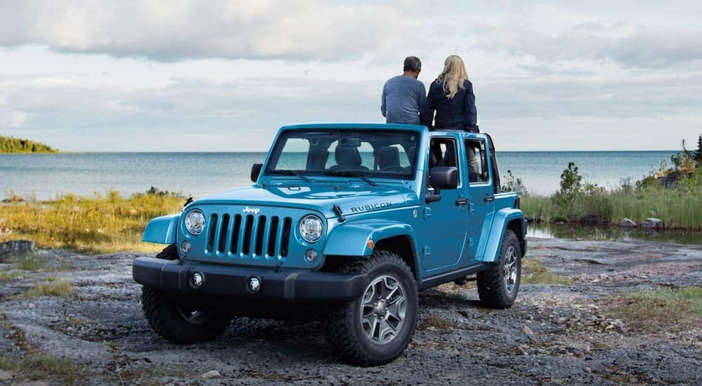 A couple is sitting on their blue 2018 Jeep Wrangler overlooking the ocean after leaving a used car dealership near me.