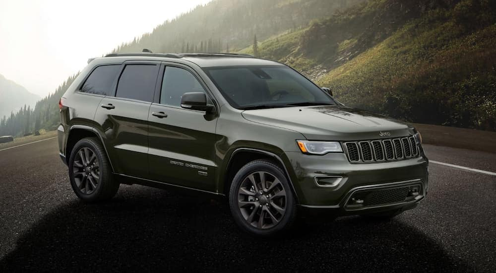 A dark green 2020 Jeep Grand Cherokee is parked on a road outside of Costa Mesa, CA.