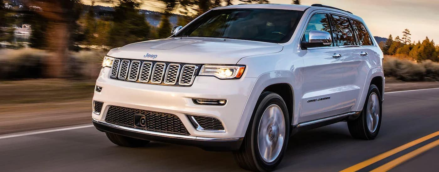A white 2017 jeep Grand Cherokee is driving on a treelined road at dusk.