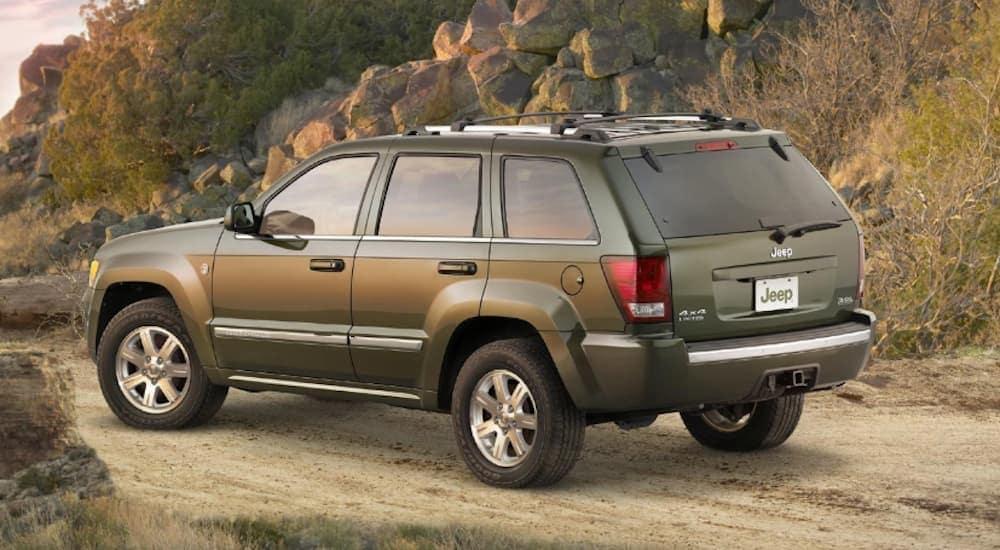 A green 2008 Jeep Grand Cherokee, which is a great choice when looking at used Jeeps for sale, is parked on a dirt trail near Costa Mesa, CA.