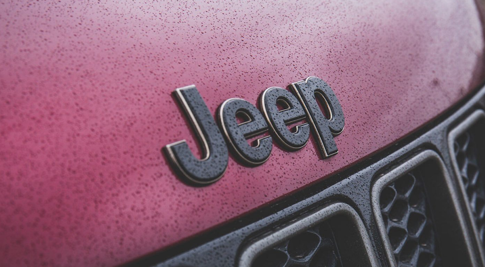 A close up of a black Jeep logo on a red Grand Cherokee is shown.
