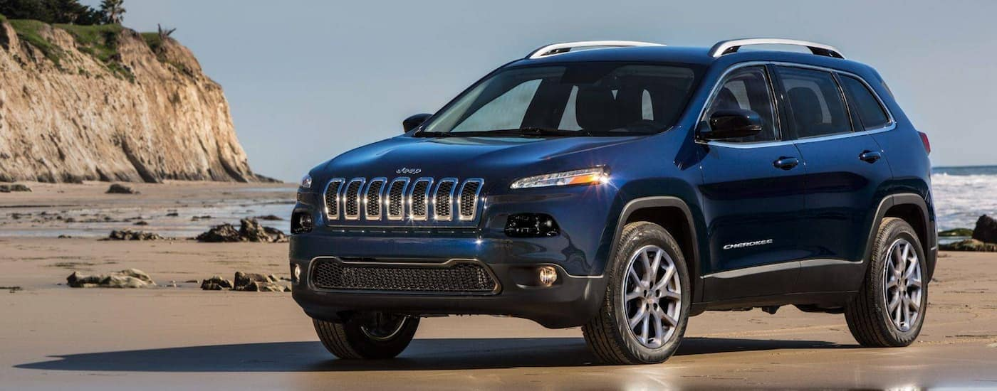 A blue 2016 Jeep Cherokee, which is a popular among used Jeeps for sale, is parked on a beach near Costa Mesa, CA.
