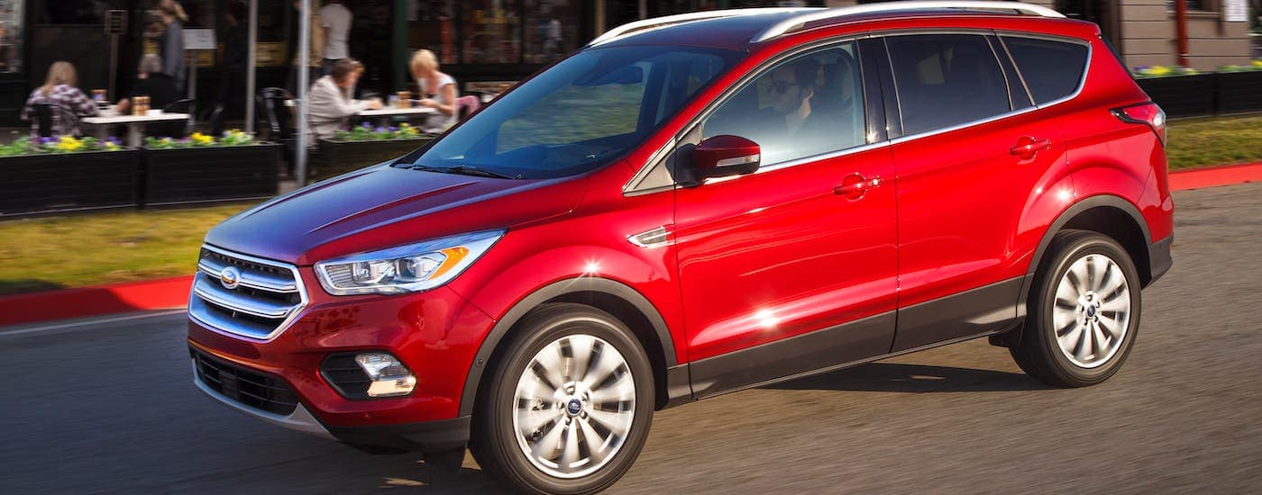 A red 2017 Ford Escape drives by a cafe after searching Used Cars Near Me Costa Mesa, CA
