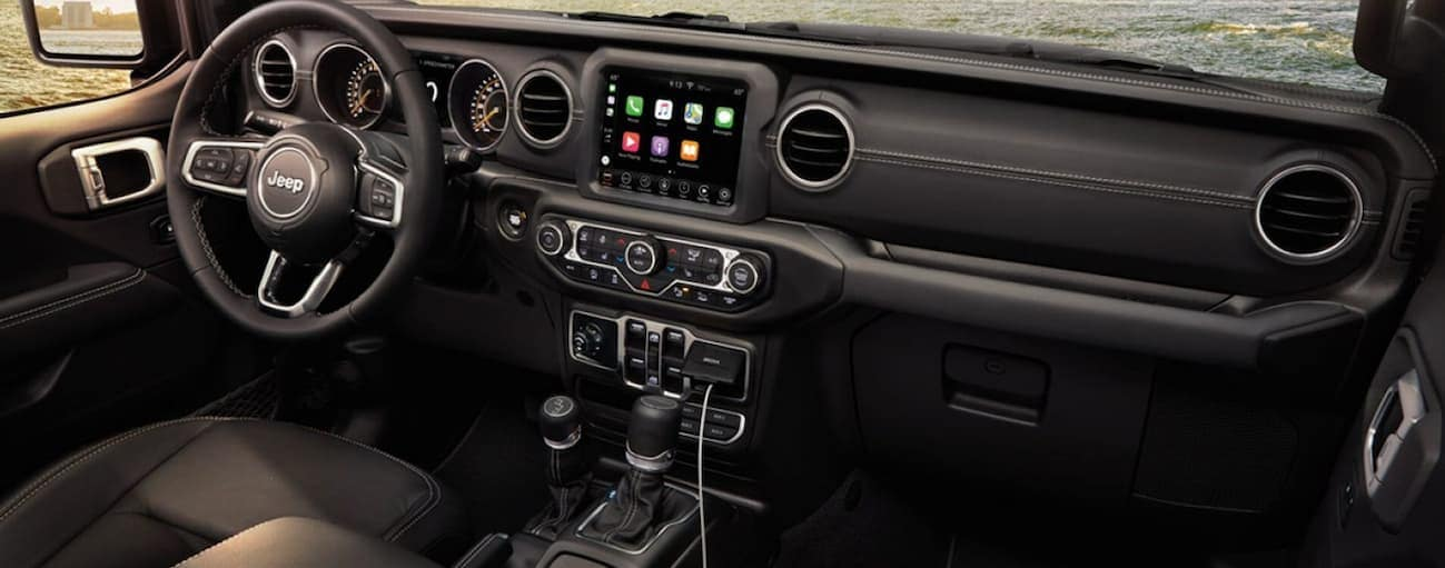 The front black leather interior of a 2020 Jeep Gladiator is shown with in an infotainment system.
