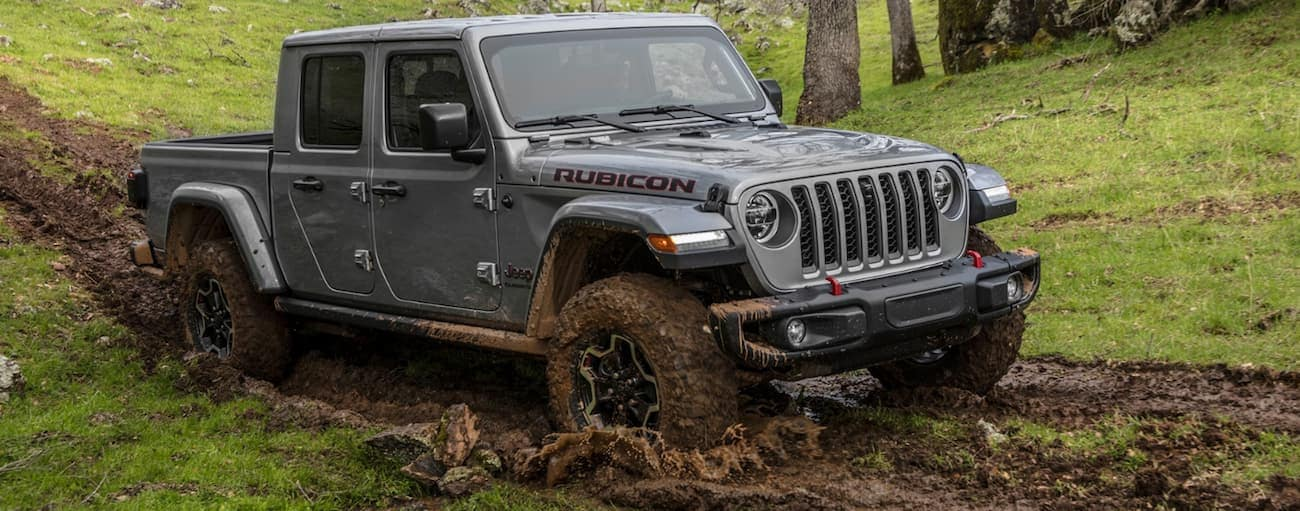 A grey 2020 Jeep Gladiator is driving through mud while off roading near Costa Mesa, CA.