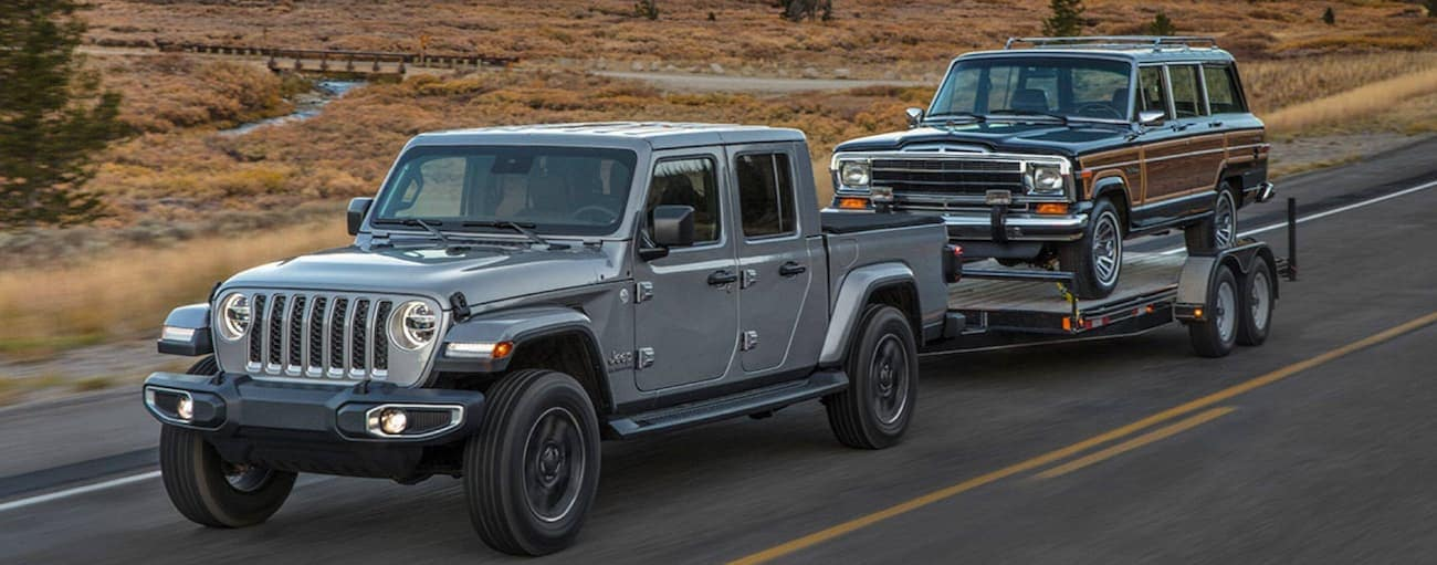 A silver 2020 Jeep Gladiator, which wins when comparing the 2020 Jeep Gladiator vs 2020 Toyota Tacoma, is towing a Jeep Wagoneer near Costa Mesa, CA.