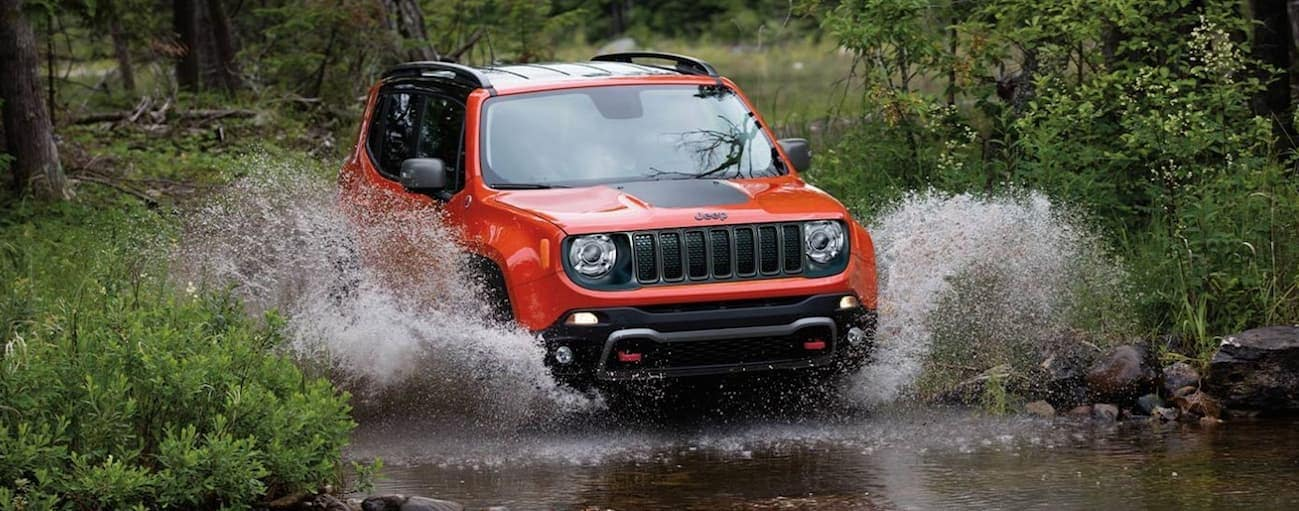 An orange 2020 Jeep Renegade is driving through a large puddle in the woods near Costa Mesa, CA.