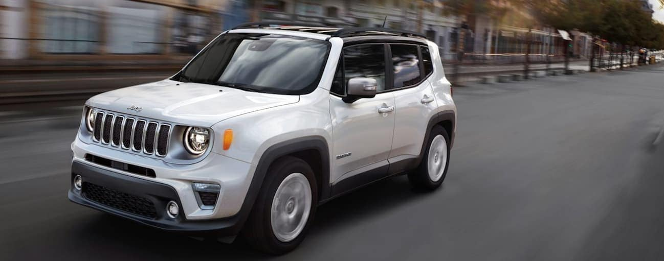 A white 2020 Jeep Renegade is driving past city buildings near Costa Mesa, CA.