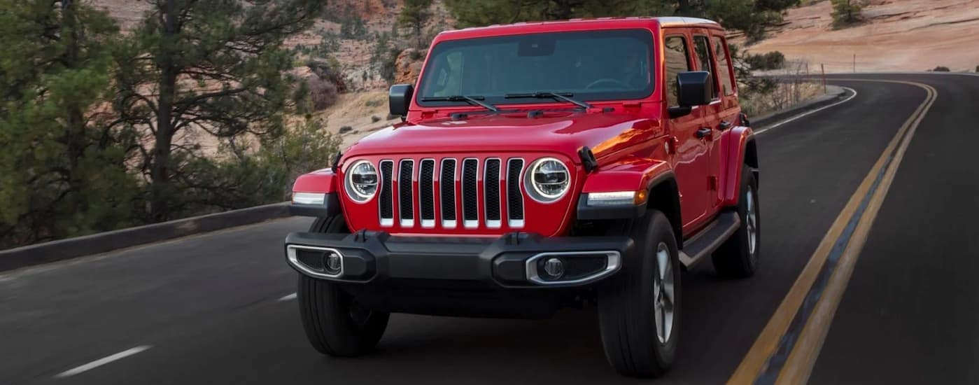 A red 2020 Jeep Wrangler is driving on a curvy road near Costa Mesa, CA.