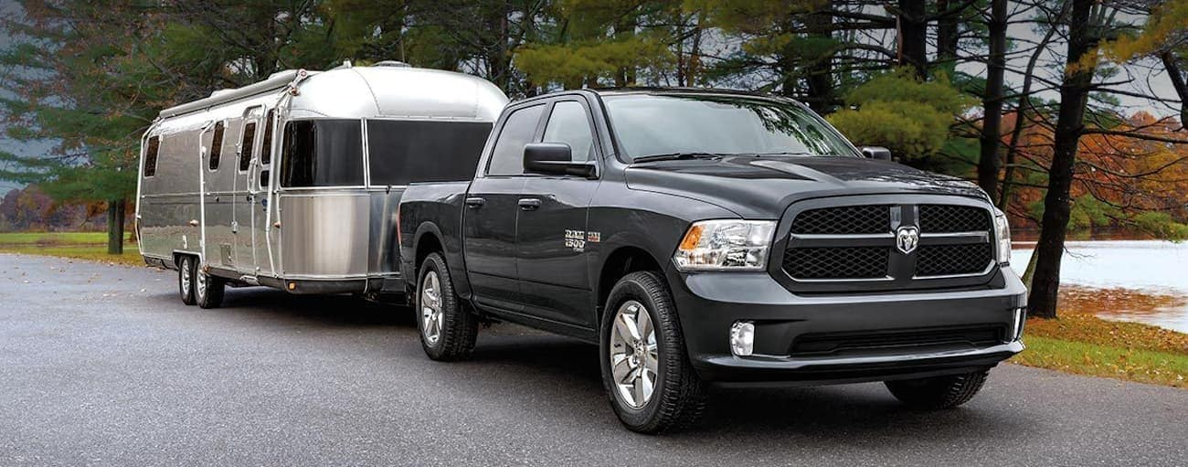 A grey 2020 Ram 1500 Classic is parked next to a lake while towing a large Airstream.