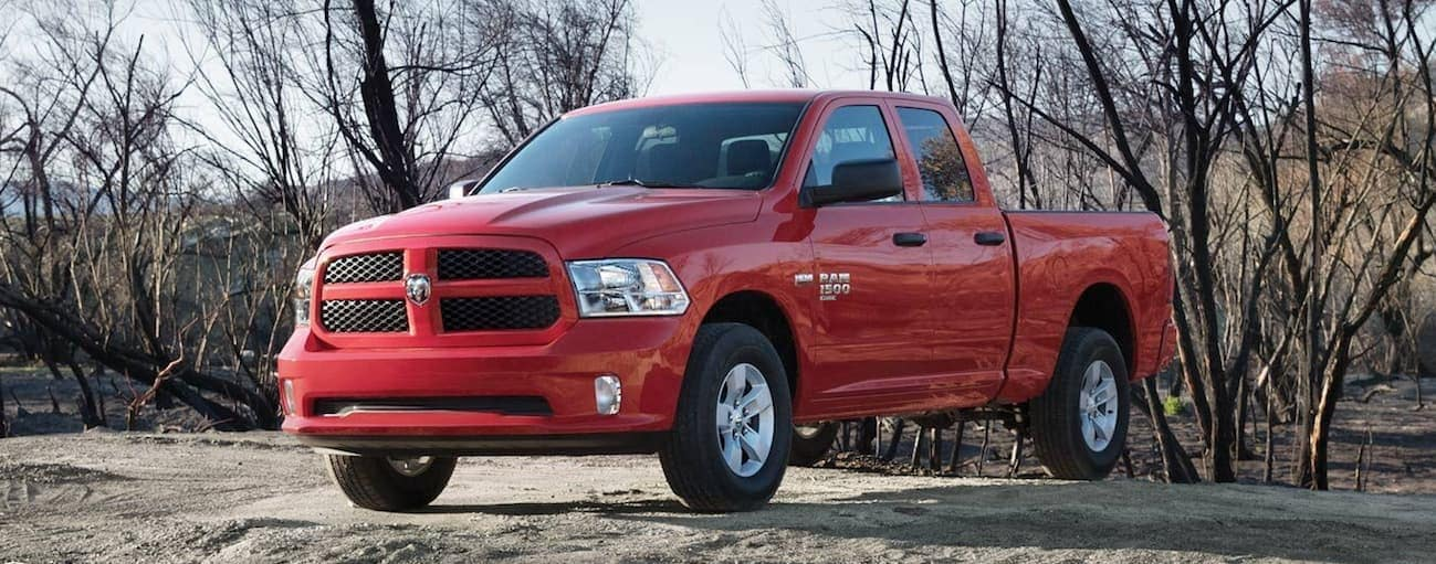 A red 2020 Ram 1500 Classic is parked on a dirt path with trees behind it.