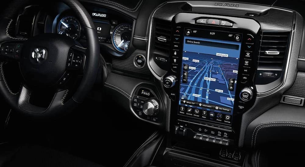 The front black interior of a 2020 Ram 1500 is shown with their 12.5 inch infotinament screen.