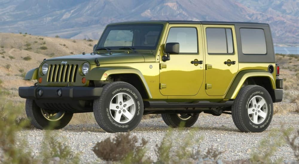 A green 2007 4-door Wrangler, which is the first year of the Jeep Wrangler Unlimited, is parked on dirt with mountains in the distance.
