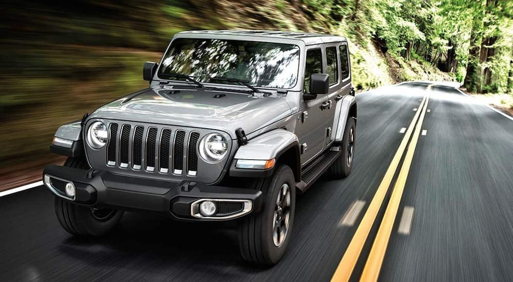 A grey 2020 Jeep Wrangler Unlimited is driving on a tree lined road near Costa Mesa, CA.