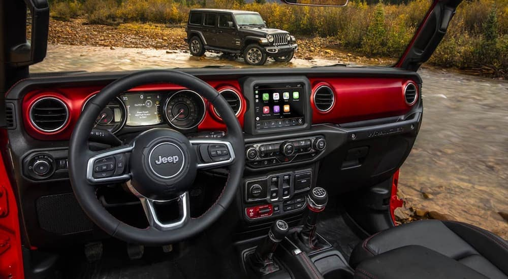 The front red and black interior of a Jeep Wrangler is shown with a grey 2020 Jeep Wrangler Unlimited in the windshield view.