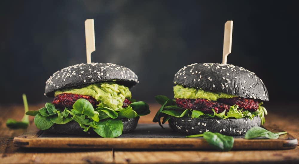 Two black vegan burgers are on a wooden platter.