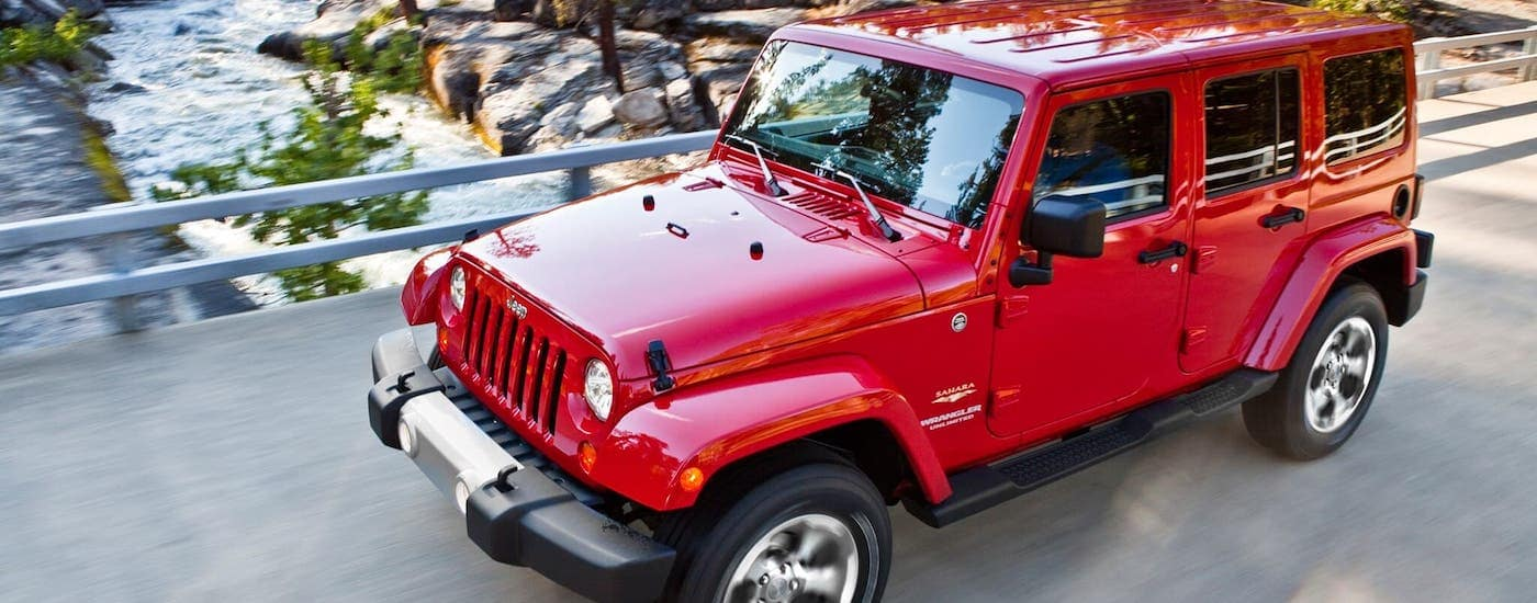 A red 2014 Jeep Wrangler Unlimited is driving over a bridge. You can find these used cars near Costa Mesa, CA.