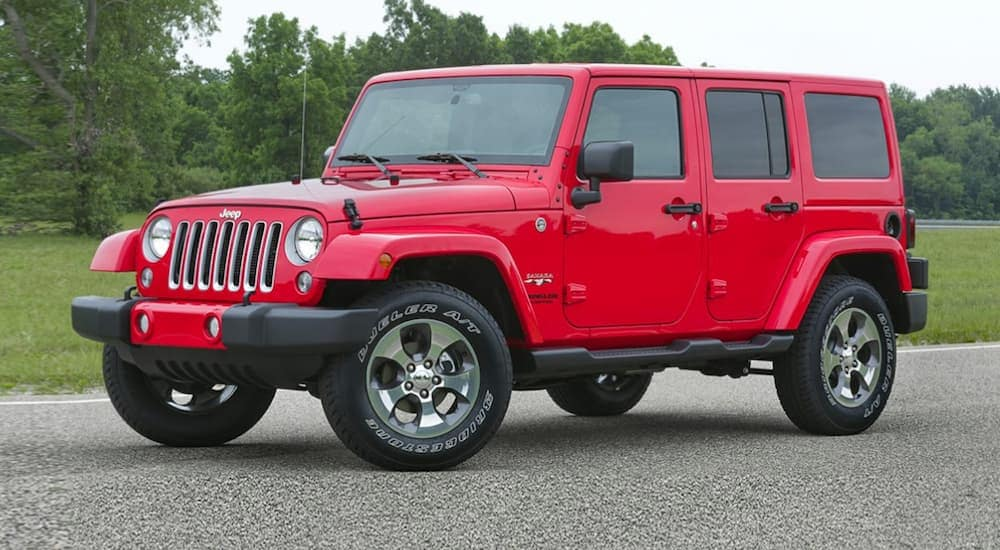 A red 2017 Jeep Wrangler, which is a popular option among used cars near me, is parked in a tree lined parking lot near Costa Mesa, CA.