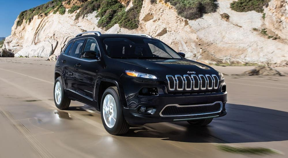 A black 2018 Jeep Cherokee, which is a popular option for used cars near me, is driving on a beach.
