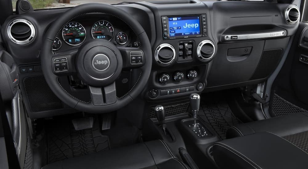 The front black leather interior of a 2014 Jeep Wrangler is shown.