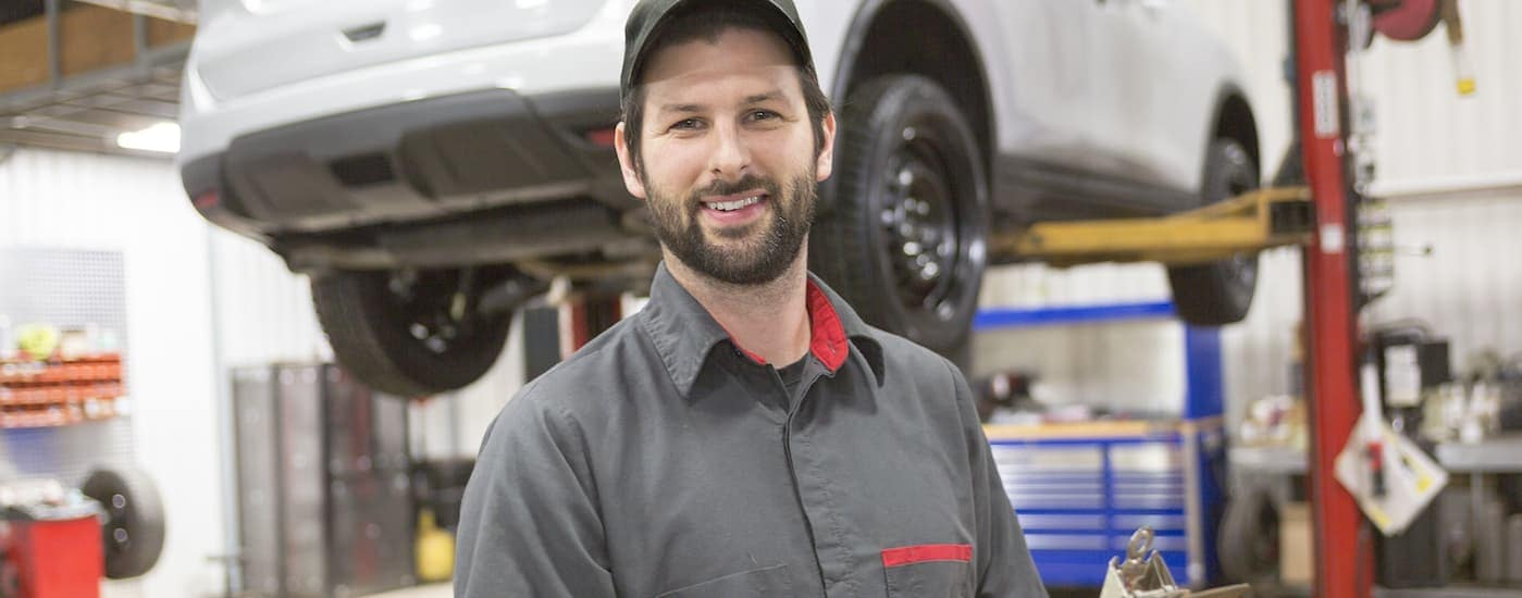 A smiling mechanic is standing in a garage with a blurred car behind him.
