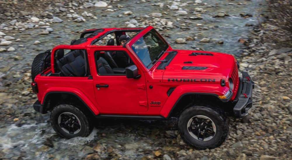 A birds eye view of a red 2020 Jeep Wrangler is parked in a rock floored stream near Costa Mesa, CA.