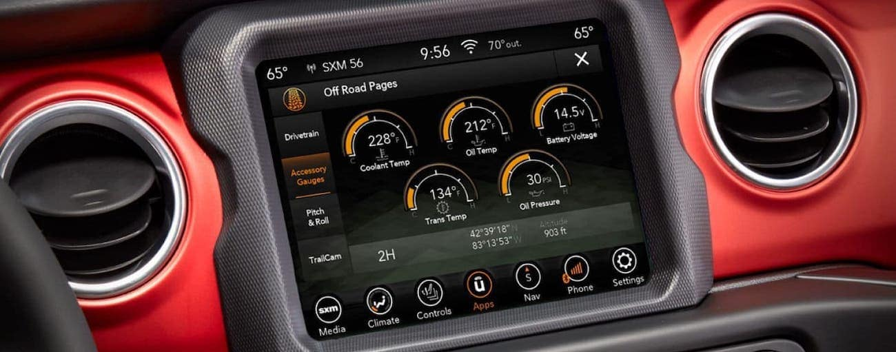 A closeup view of the infotainment screen in a red 2020 Jeep Gladiator in Costa Mesa, CA.