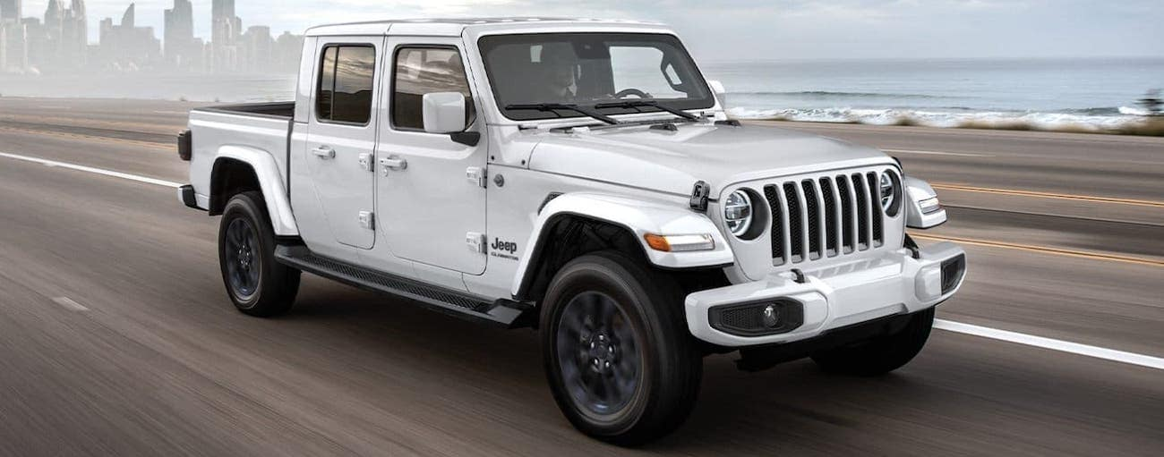 A white 2020 Jeep Gladiator is driving off with a win after 2020 Jeep Gladiator vs 2020 Ford Ranger.