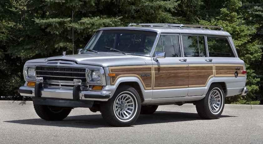 A blue and wood-paneled 1989 Jeep Grand Wagoneer is parked in front of trees.