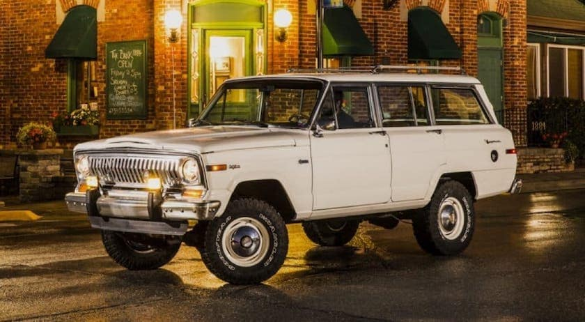 A classic white Jeep Wagoneer is driving on a city street outside Costa Mesa, CA.