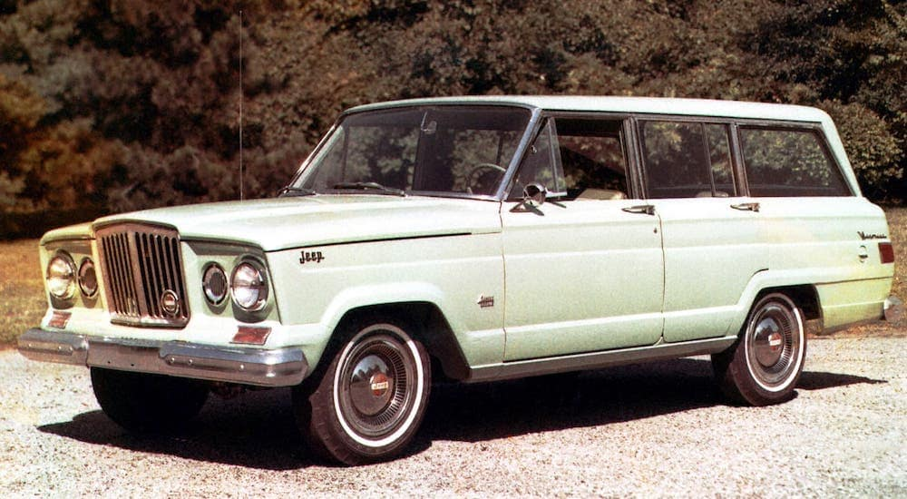 A green 1960s Jeep Wagoneer is parked in front of trees.