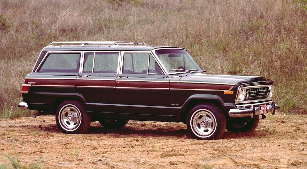 A black and wood-paneled 1970s Jeep Wagoneer is parked in front of a field outside Costa Mesa.