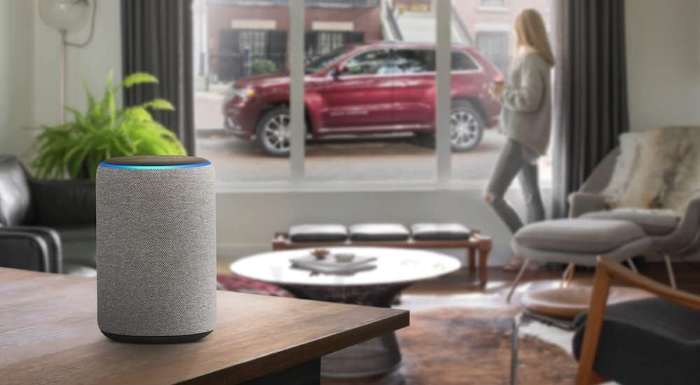 A woman is looking out the window at a red 2020 Jeep Grand Cherokee while an Alexa is in the foreground.