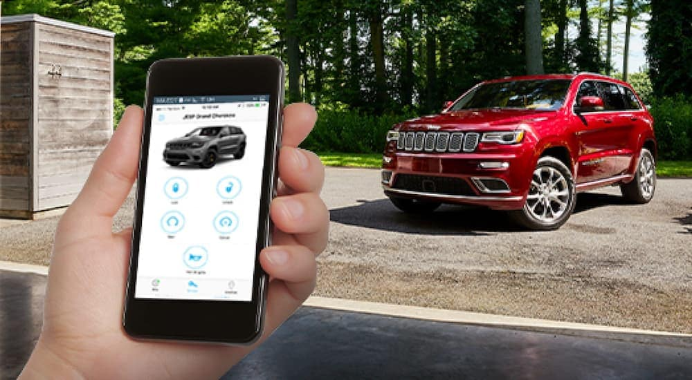 A phone is showing the remote start feature in a Costa Mesa, CA, garage, while the red 2020 Jeep Grand Cherokee is parked outside.