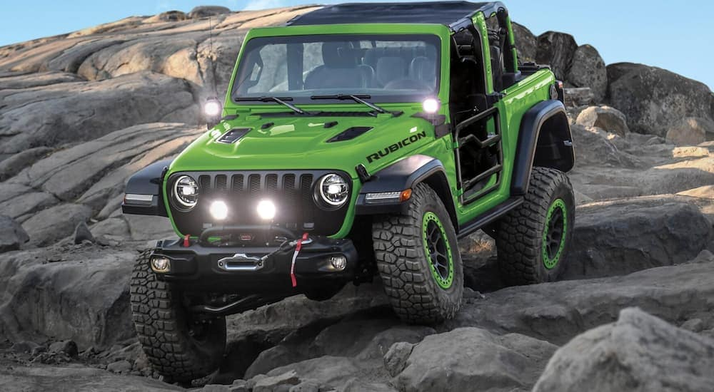 A green Jeep Wrangler JL with Mopar parts is off-roading on rocks.