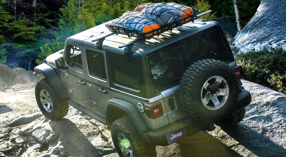 A silver Jeep Wrangler Rubicon, which is popular among Jeeps for sale, is off-roading with a roof rack.