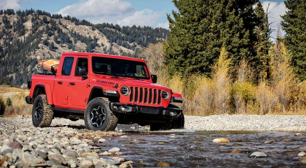 A red 2020 Jeep Gladiator, a newer Jeep for sale, is crossing a river with mountains in the distance.