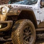 A white 2020 Jeep Wrangler is covered in mud on a trail near Costa Mesa, CA.