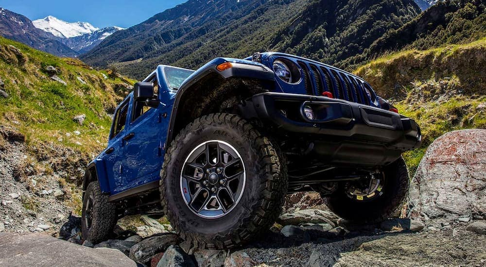A blue 2020 Jeep Wrangler is off-roading in the mountains.