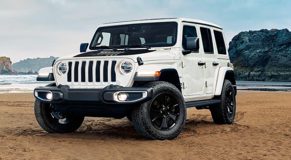 A white Jeep Wrangler Sahara is parked on the beach near Costa Mesa, CA.