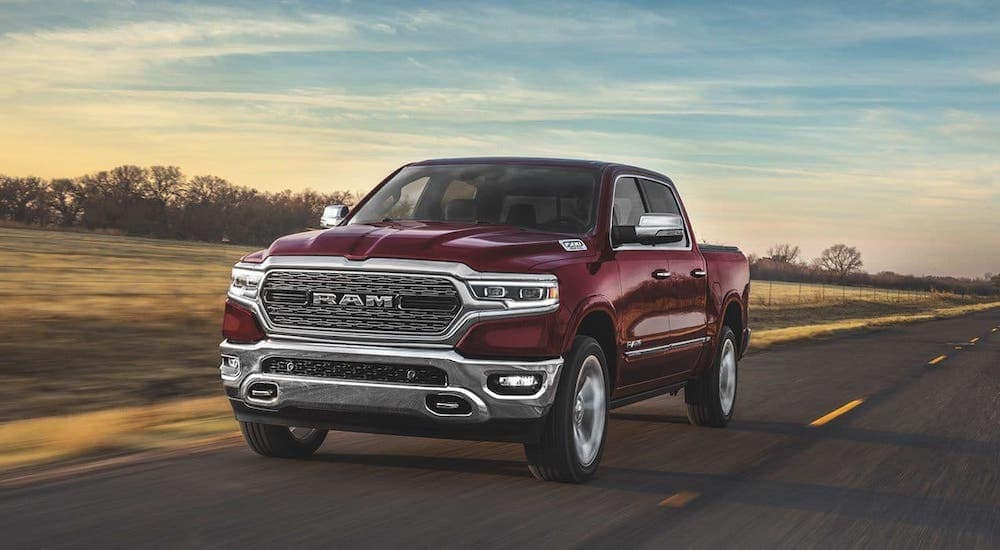 One of the popular Ram Trucks in Costa Mesa, a red 2020 Ram 1500, is driving on a highway.