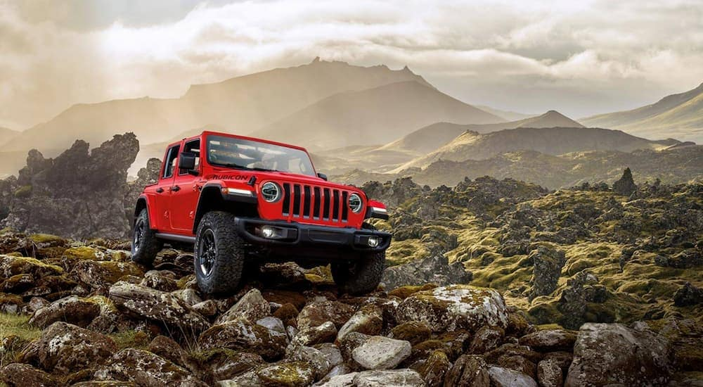 A red 2020 Jeep Wrangler Unlimited is off-roading in the mountains.