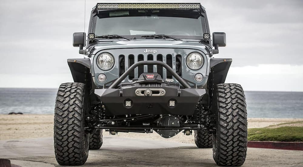 A grey Stealth Edition Jeep Wrangler from OC Motorsports in Costa Mesa, CA, is shown parked at the ocean from the front.