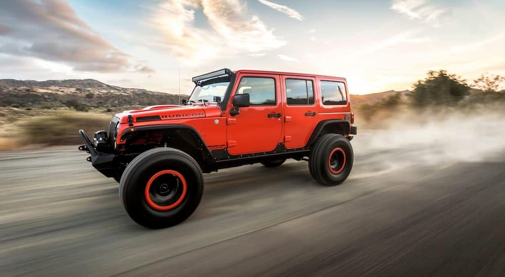 The OJ edition Jeep Wrangler Unlimited in red is shown driving on a dusty road after leaving a used car dealer.