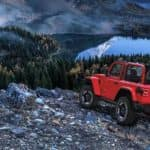A red 2020 Jeep Wrangler is parked above a mountain lake while off-roading after leaving a Jeep dealership in Costa Mesa, CA.