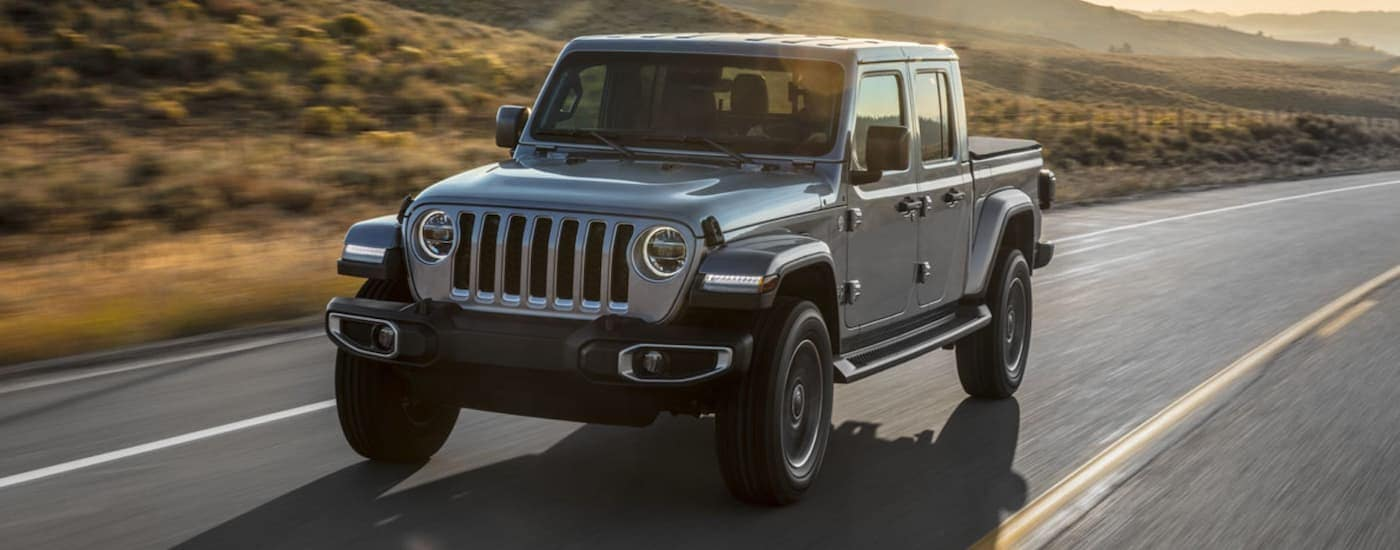 A silver 2020 Jeep Gladiator is driving past hills with a sun flare above it.