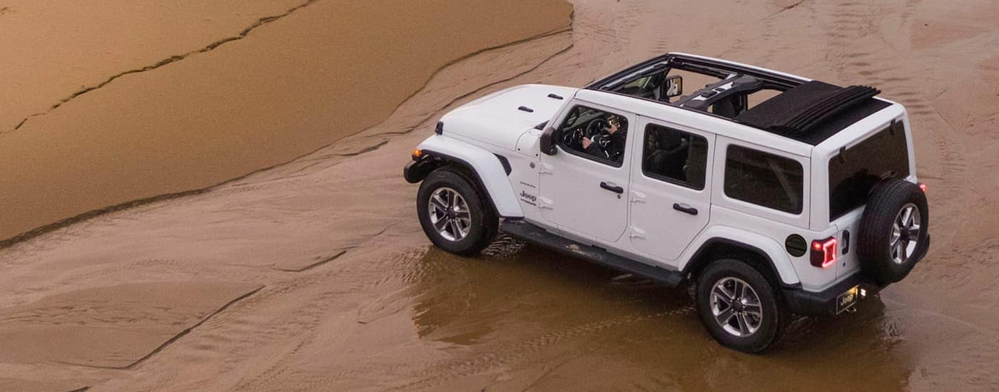 A white 2020 Jeep Wrangler Unlimited is parked on the beach shore after leaving a Jeep dealership near me in Costa Mesa, CA.