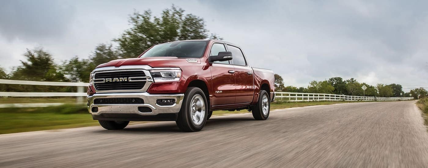 A red 2020 Ram 1500 Big Horn is driving past a white farm fence.