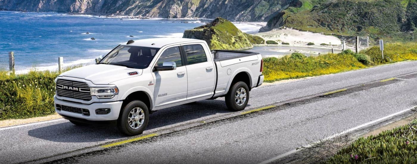 A white 2020 Ram 2500 is driving past the ocean near Costa Mesa, CA, after leaving a Ram dealer near me.